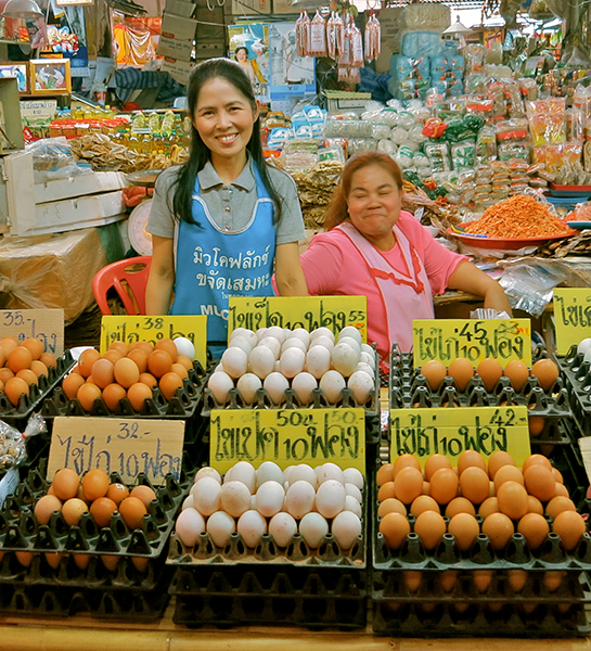 Happy faces selling eggs at a Khorat street market.